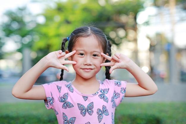 Retrato da menina asiática pequena feliz da criança com as orelhas de gato que guardam os dedos em sua cara.