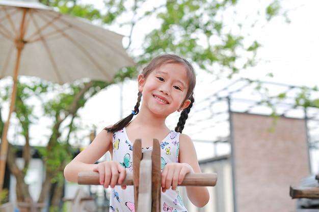 Retrato da menina asiática pequena feliz que joga o cavalo de madeira do brinquedo no jardim exterior.