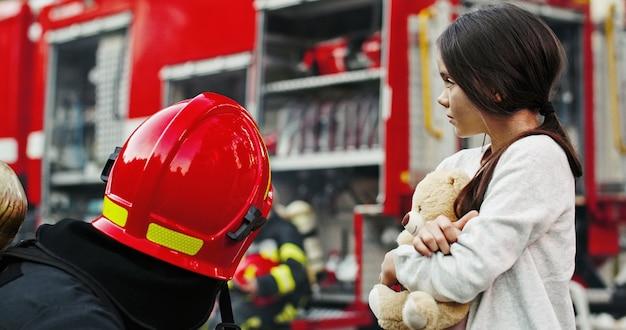 Retrato da menina asiática pequena resgatada com o homem do sapador-bombeiro que está o caminhão de bombeiros próximo. bombeiro em operação de combate a incêndio