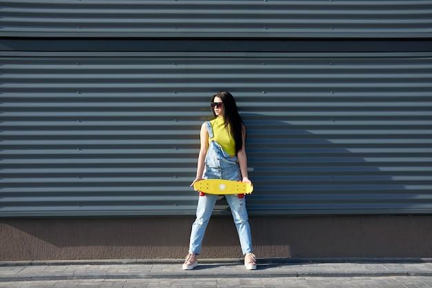 Retrato da menina atrativa nova positiva que veste a parte superior e a calças de ganga amarelas com skate amarelo.