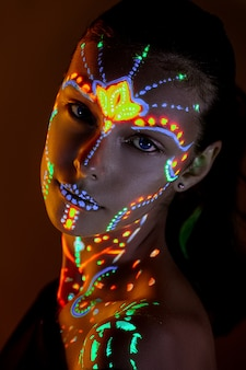 Retrato da menina bonita com pintura ultravioleta em sua cara. menina com composição de néon na luz da cor.