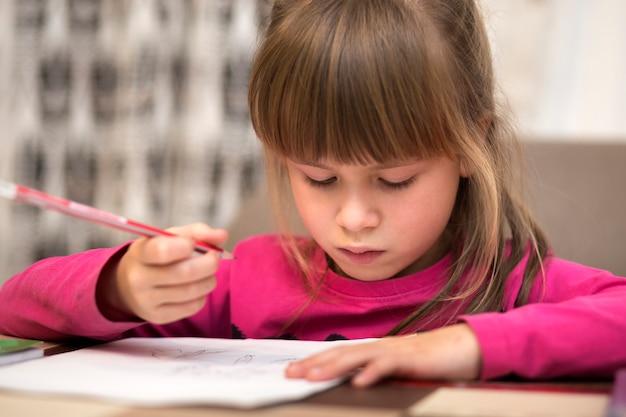 Retrato da menina bonita consideravelmente pequena da criança séria que desenha com o lápis no papel. arte educação, criatividade, fazendo lição de casa e conceito de atividades de crianças.