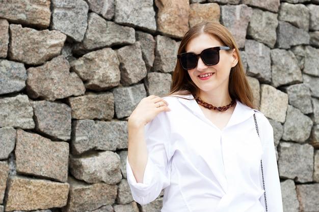 Retrato da menina bonita em óculos de sol no fundo de concreto cinza