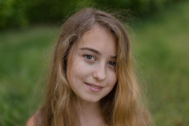 Retrato da menina bonita fora de sentar e sorrir durante o dia.