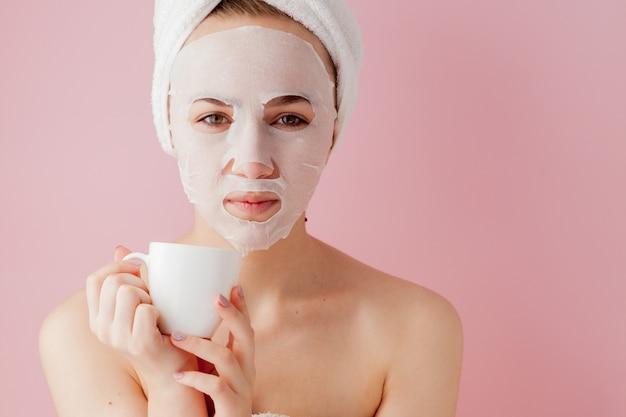 Retrato da menina bonita no roupão de banho com uma xícara de chá, mulher loura do conceito do abrandamento que veste o roupão e a toalha na cabeça após o banho.