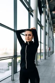Retrato da menina bonita no sportwear preto que estica seus braços.