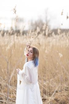 Retrato da menina bonita nova no vestido branco no campo de trigo, andando, despreocupado.