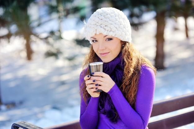 Retrato da menina bonita que bebe a bebida quente no inverno nevado.