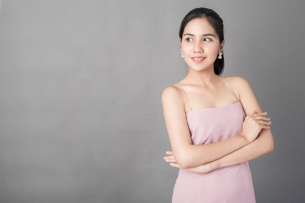 Retrato da menina bonita saudável no vestido cor-de-rosa no fundo cinzento, tiro do estúdio