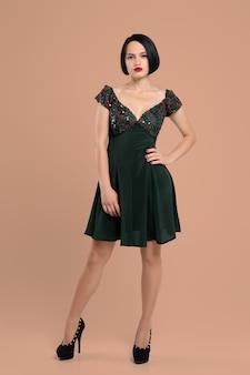 Retrato da menina bonito no vestido curto e em sapatos de salto alto posando com a mão na cintura no estúdio