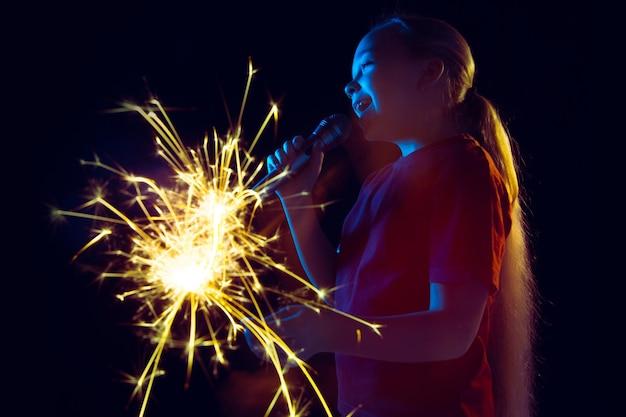 Retrato da menina caucasiana em fundo escuro do estúdio em luz de néon. linda modelo feminino com alto-falante e diamante.