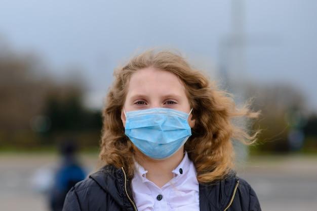 Retrato da menina caucasiano triste na máscara protetora na cidade e no parque ao ar livre. quarentena à distância social do coronavírus.