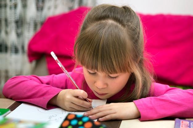 Retrato da menina consideravelmente pequena bonito da criança séria que tira com o lápis no papel. arte educação, criatividade, fazendo lição de casa e conceito de atividades de crianças.