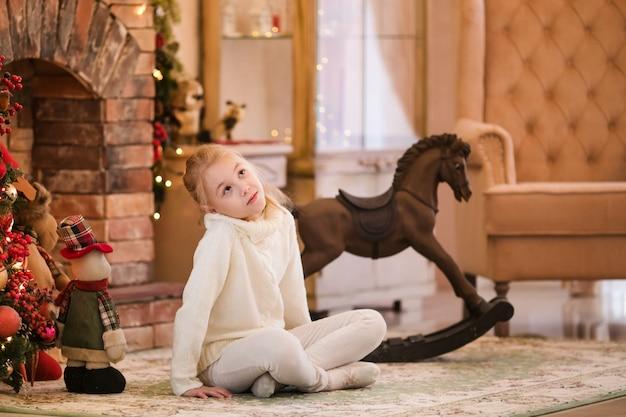 Retrato da menina criança loira feliz está sentado em casa