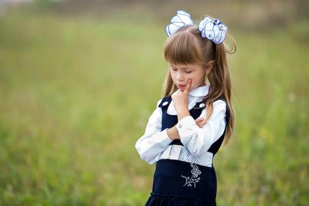 Retrato da menina da primeira série em uniforme escolar