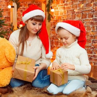 Retrato da menina de cabelos louro bonitinha sentada no chão perto de presentes de natal