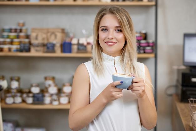 Retrato da menina de sorriso que mantém a xícara de café, olhando a câmera.