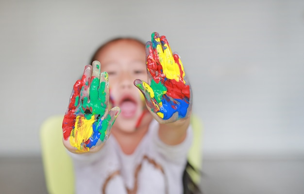 Retrato da menina de sorriso que olha através de suas mãos coloridas e bochecha pintadas na sala das crianças.