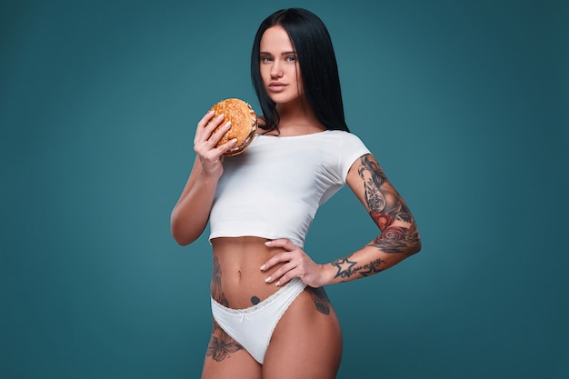 Retrato da menina encantadora tatuagem bonita segurando o hambúrguer