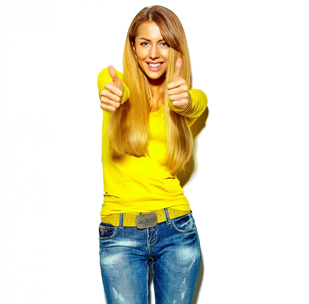 Retrato da menina feliz bonita sorridente mulher loira bonita em roupas de verão casual sem maquiagem isolada no branco mostrando os polegares para cima o sinal