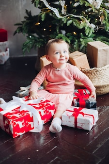 Retrato da menina feliz que senta-se no telhado na sala decorada e que joga com presentes de natal.