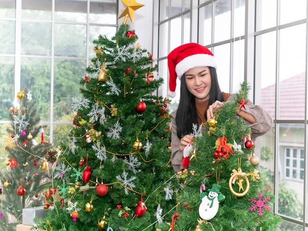 Retrato da menina feliz que veste o tampão vermelho que decora a árvore de natal em casa.