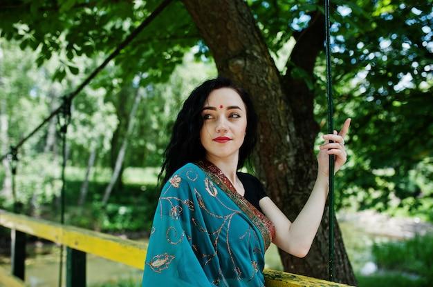 Retrato da menina indiana bonita do brumette ou do modelo hindu da mulher na ponte. traje indiano tradicional lehenga choli.