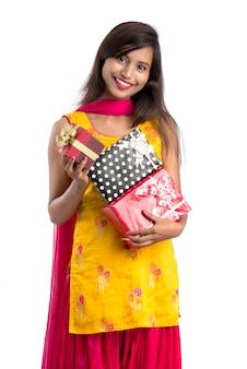 Retrato da menina indiana de sorriso feliz nova que guarda caixas de presente em um fundo branco.
