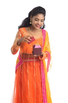 Retrato da menina indiana de sorriso feliz nova que guarda caixas de presente em uma parede branca.