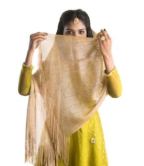 Retrato da menina indiana tradicional bonita que levanta no espaço em branco.