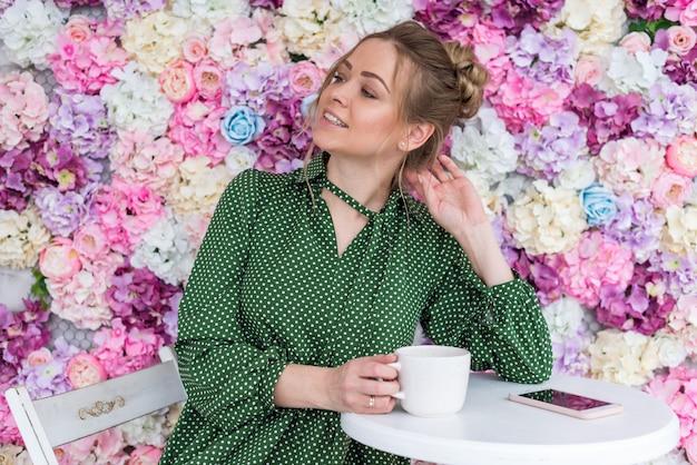 Retrato da menina loira se senta à mesa no café contra um fundo floral com vista orgulhosa