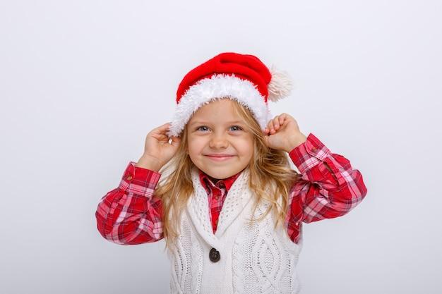 Retrato da menina loira sorridente no chapéu de papai noel no fundo branco
