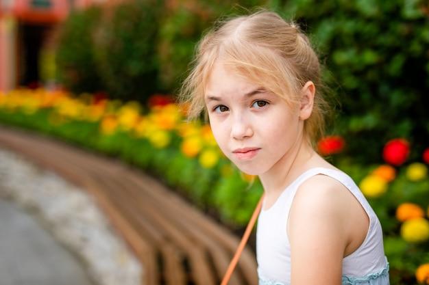 Retrato da menina loura triste com olhos castanhos ao ar livre no verão
