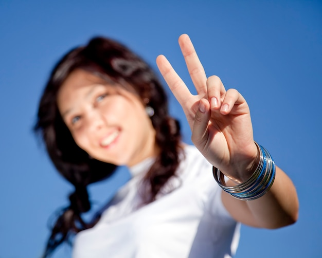 Retrato da menina moreno bonita com olhos azuis que mostram o símbolo da mão v.