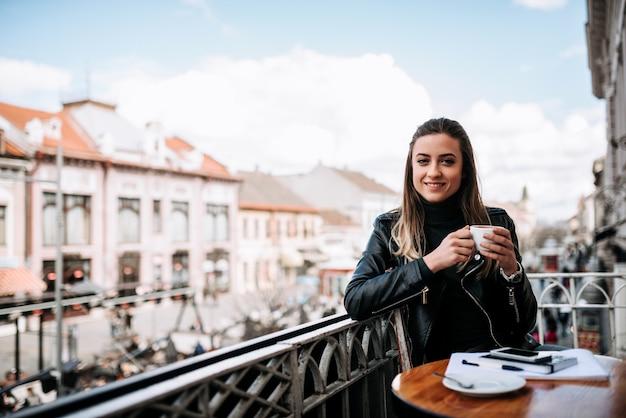 Retrato da menina moreno bonita que come uma xícara de café em um teracce na cidade.