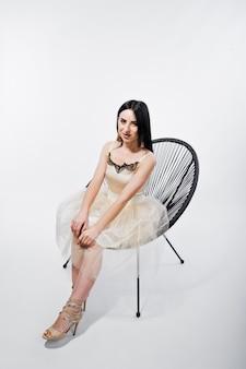 Retrato da menina moreno no vestido bege com a cadeira isolada no branco.