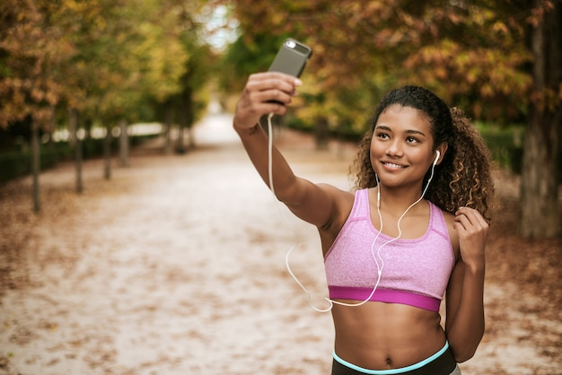 Retrato da menina nova e atrativa dos esportes que toma um selfie em seu telefone e música de escuta no parque.