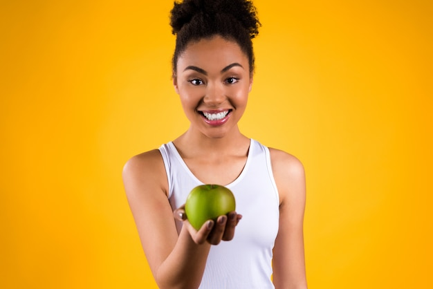Retrato da menina preta com a maçã verde isolada.