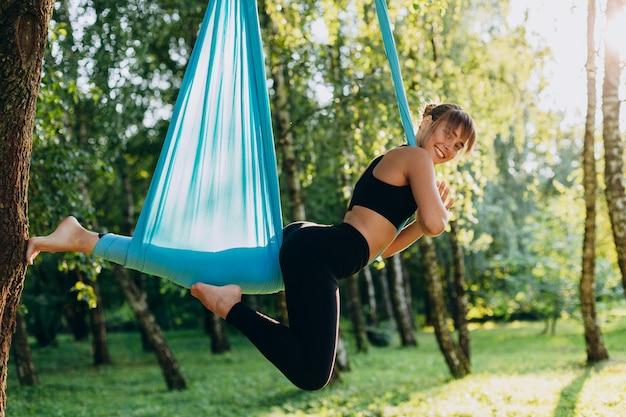 Retrato da menina que faz a ioga da mosca na árvore ao ar livre e olhando a câmera.