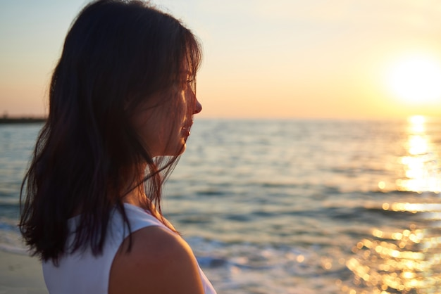 Retrato da menina que olha no por do sol bonito do mar.
