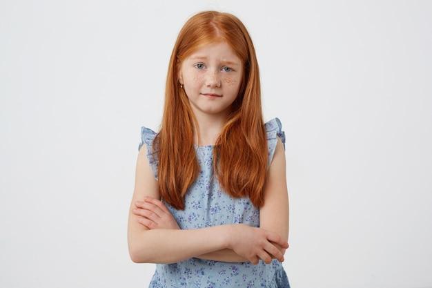 Retrato da menina ruiva de sardas infelizes com duas caudas, descontente olha para a câmera, usa um vestido azul, fica com os braços cruzados sobre fundo branco.