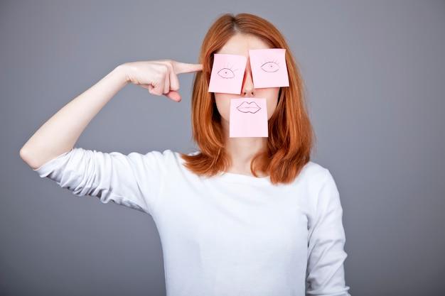 Retrato da menina ruivo com etiquetas engraçadas coloridas na boca e nos olhos.