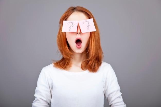 Retrato da menina ruivo com etiquetas engraçadas coloridas nos olhos.