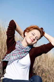 Retrato da menina ruivo feliz na grama do outono.