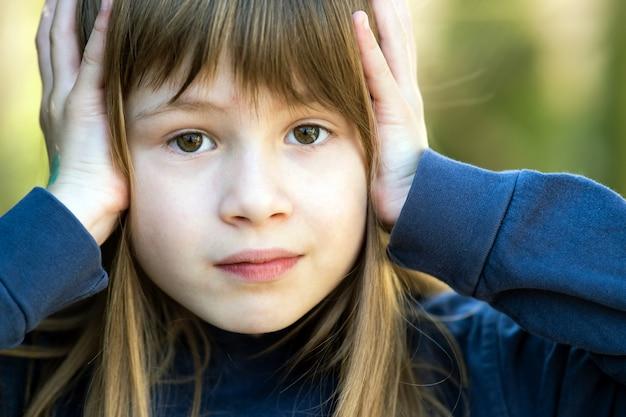 Retrato da menina surpreendida da criança que guarda as mãos a sua cabeça fora no verão. criança do sexo feminino chocada em um dia quente lá fora.