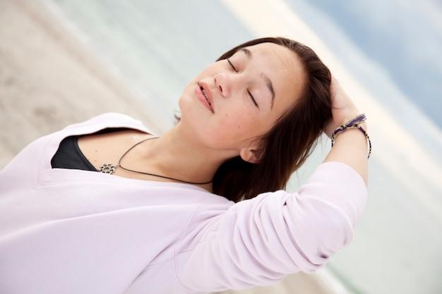 Retrato da menina triguenha bonita na praia.