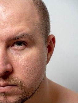 Retrato da metade do rosto de um homem de meia-idade, olhando para a câmera. barba, cabelinho na cabeça. foto vertical
