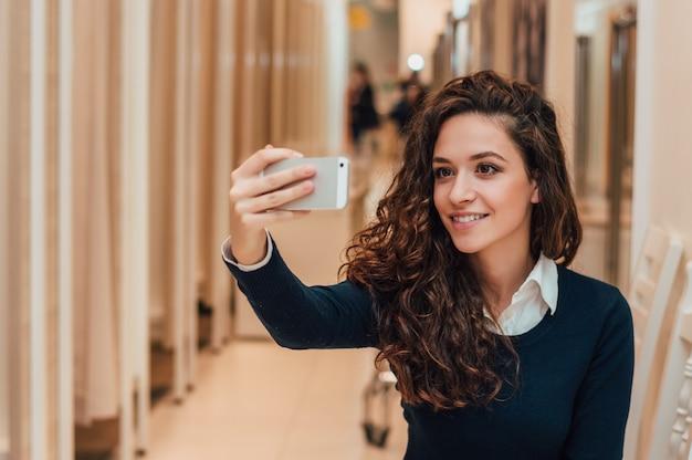 Retrato da moça bonita que toma o selfie usando o smartphone no vestuário, vestuario.