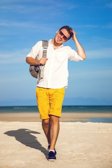 Retrato da moda ao ar livre de homem bonito em roupa casual da moda brilhante caminhando em uma praia tropical