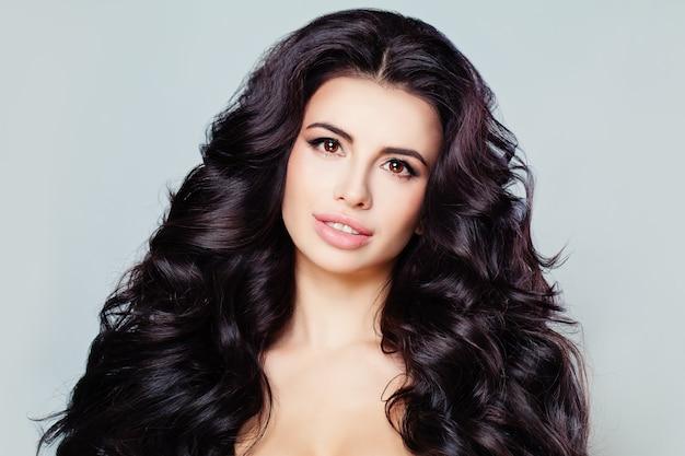 Retrato da moda beleza da modelo de mulher bonita com pele fresca, maquiagem diária e penteado ondulado. cabelo comprido e brilhante, lábios sensuais e sobrancelhas escuras